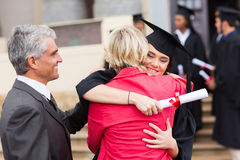 Graduate hugging mother. Happy female graduate hugging her mother after graduation Royalty Free Stock Images
