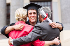 Graduate hugging parents. Handsome young male graduate hugging his parents at graduation Stock Photos