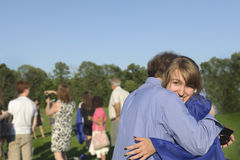 Graduate hugs her dad after commencement. Pretty female graduate hugs her dad after commencement exercises. Although graduation marks the end of school (here stock images