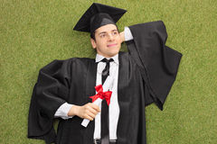 Graduate lying on grass and daydreaming. Young college graduate lying on grass with diploma in his hand and daydreaming Royalty Free Stock Image