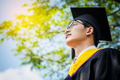 A graduate in the mantle looks up and thinks of a great future. Handsomel graduate boy with graduate, Nature background royalty free stock photo