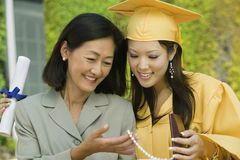 Graduate and mother admiring necklace gift outside Stock Image