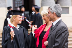 Graduate with parents. Happy female university graduate with parents at graduation ceremony Stock Photography