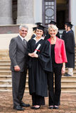 Graduate with parents. Portrait of young girl graduate standing with parents at graduation ceremony Stock Photos