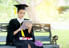 Graduate playing tablet in her hand feeling relaxing and so happiness in commencement day. And search job new stock image