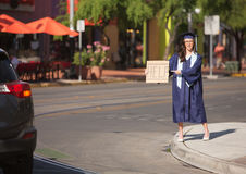 Graduate Pointing to Help Sign. College graduate standing in street with help sign Royalty Free Stock Photo