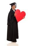 Graduate presenting heart shape Royalty Free Stock Photos