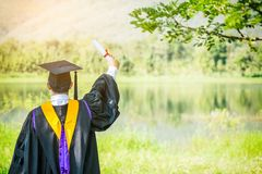 Graduate put he hands up and celebrating with certificate in he Royalty Free Stock Images