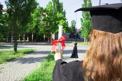 Graduate put her hands up and celebrating with certificate in her hand and feeling so happiness in Commencement day.  Stock Photos