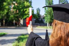 Graduate put her hands up and celebrating with certificate in her hand and feeling so happiness in Commencement day.  Royalty Free Stock Photo
