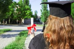 Graduate put her hands up and celebrating with certificate in her hand and feeling so happiness in Commencement day.  Royalty Free Stock Photography