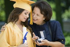 Graduate Receiving Bracelet From Grandmother Outside Stock Photo