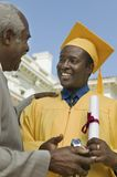 Graduate receiving present from father Royalty Free Stock Photography