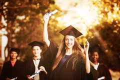 Graduate school kids standing with degree scroll in campus royalty free stock image