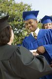 Graduate shaking hand of dean outside Royalty Free Stock Images