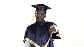 Graduate showing thumbs down. White. Close up. Graduate showing thumbs down, graduate in a special form and in glasses raises his hand and shows a lowered thumb stock footage
