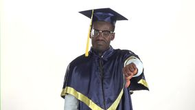 Graduate showing thumbs down. White. Slow motion. Close up. Graduate showing thumbs down, graduate in a special form and in glasses raises his hand and shows a stock video