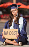 Graduate Sitting with Debt. Serious Caucasian female graduate sitting on sidewalk with debt sign Stock Photos