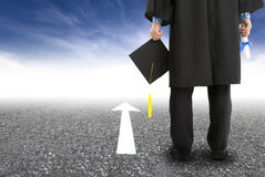 Graduate standing on the road. Graduate student standing on the road and forward arrow Royalty Free Stock Images