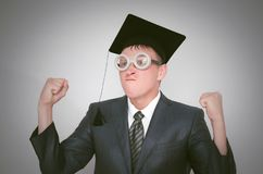 Graduate student. Angry graduate student in the cap is shaking a fist isolated on gray background. Education concept royalty free stock photo