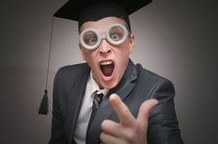 Graduate student. Angry graduate student in the cap isolated on gray background. Education concept royalty free stock image