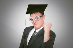 Graduate student. Angry graduate student in the cap is shaking a fist isolated on gray background. Education concept stock photos
