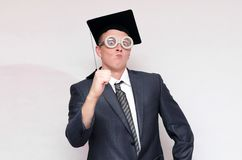Graduate student. Disgruntled and arrogant graduate student in the cap isolated on gray background. Education concept stock image