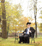 Graduate student holding diploma and book in park Royalty Free Stock Images