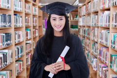 Graduate student holding a diploma in library Royalty Free Stock Images