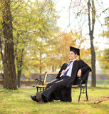 Graduate student holding diploma in park. Graduate student holding diploma seated on bench in park shot with tilt and shift lens Royalty Free Stock Photos