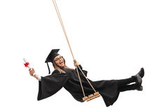 Graduate student holding diploma and swinging on swing Royalty Free Stock Photo