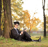 Graduate student holding a tablet seated on grass. Graduate student holding a tablet in park and looking at the camera seated on the grass shot with tilt and Stock Image