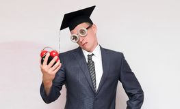 Graduate student. Irritated graduate student looking on the red alarm clock in his hand isolated on gray background. Education concept royalty free stock photos