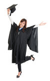 Graduate student jumping. Full body excited Asian female student in graduation gown hands raised open arms jumping isolated on white background Royalty Free Stock Image