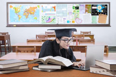 Graduate student learns on desk in the class Stock Images