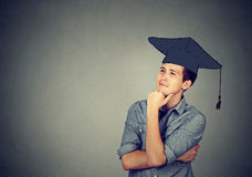 Graduate student man in cap gown looking up thinking. Portrait thoughtful graduate student young man in cap gown looking up thinking isolated gray wall Stock Images