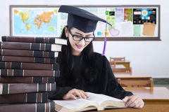 Graduate student with mortarboard reading books Stock Images