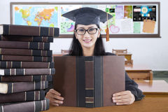 Graduate student with mortarboard studying in class Stock Image