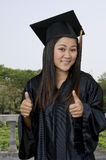 Graduate student outdoors with two thumbs up Royalty Free Stock Images