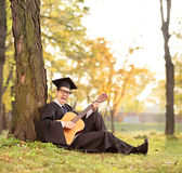Graduate student playing acoustic guitar in park. Shot with a tilt and shift lens Royalty Free Stock Image