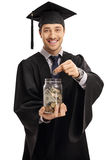 Graduate student putting a coin into a jar Stock Photo