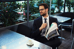 Graduate student reading a newspaper advertisement about work and drink coffee. Young brunette hair businessman holding a newspaper outdoors at a coffee shop stock images