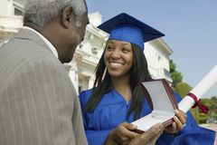 Graduate Student Receiving Gift From Father Royalty Free Stock Image