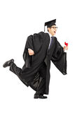 Graduate student running and holding a diploma. Full length portrait of graduate student running and holding a diploma isolated on white background Royalty Free Stock Photography
