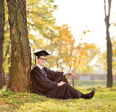 Graduate student sitting by a tree in a park Stock Photos