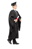 Graduate student walking with diploma in his hand Royalty Free Stock Image