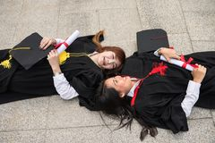 Graduate students in Commencement day. Portrait of Asian beautiful young female students with black graduation gowns hold diploma and lie down on floor. Happy Stock Photos