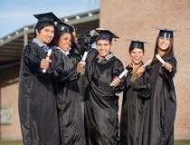 Graduate Students Holding Certificates On Stock Photo