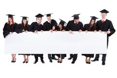 Graduate students holding empty banner. Isolated on white Royalty Free Stock Photography