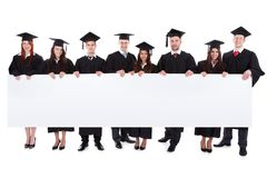 Graduate students holding empty banner Royalty Free Stock Photography
